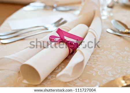 Banquet table setting with menu tied with pink ribbon