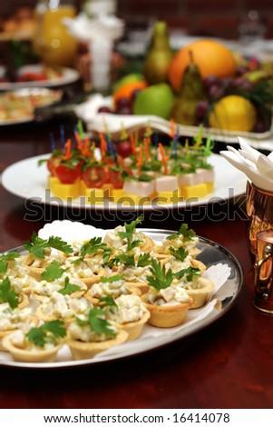 Banquet table. Tart-lets, salads and fruit basket with apple, orange, grapes and juice on a background (focus on tartlets).