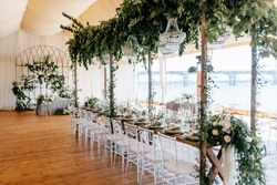 Banquet tables decorated with arrangements of flowers, herbs and candles in the tent. Wedding. Banquet.Crystal chandeliers hang from above
