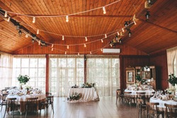 Banquet wooden hall for a rustic wedding with round decorated tables, Viennese chairs with flowered leaves and tablecloths. Horizontal