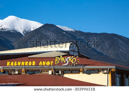 Bansko, Bulgaria - February 19, 2015: The roof and name with Bansko ski station, cable car lift, Bulgaria. Snow mountain peaks and blue sky at the background