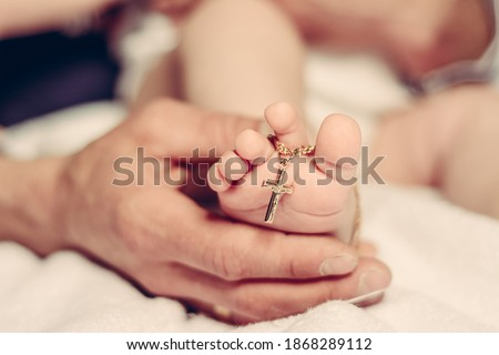 Photo of  Baptism of a baby, close up of tiny baby feet, sacrament of baptism.