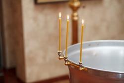 Baptizing ceremony preparation. Burning Candles on baptismal font.