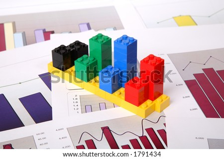 Bar chart built out of coloured toy building block on a paper chart background