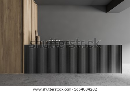 Bar counter in modern coffee shop with grey and wooden walls and concrete floor. Coffee machine with porcelain and paper cups. 3d rendering