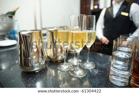Bar counter with champagne, bartender in background