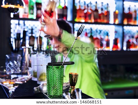 Bar inventory at nightclub. Barman professional making cocktail drinks in background soft focus