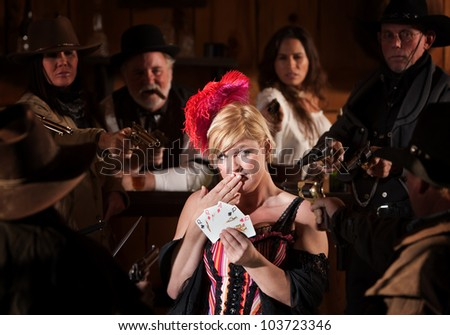 Bar maid with cards and people with guns aimed at her - stock photo