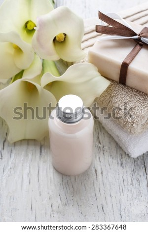 Bar of handmade natural soap, liquid soap, towels and bouquet of white calla flowers on rustic wooden table