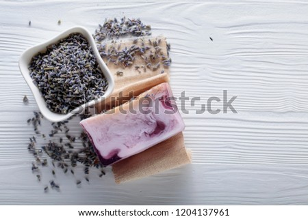 Bar of natural organic soap with lavender on white wooden background. Handmade soap making. Spa products and skin care concept. Copy space.