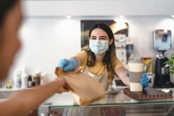 Bar owner working only with take away orders during corona virus outbreak - Young woman worker wearing face surgical mask giving takeout meal to customers - Healthcare and Food drink concept