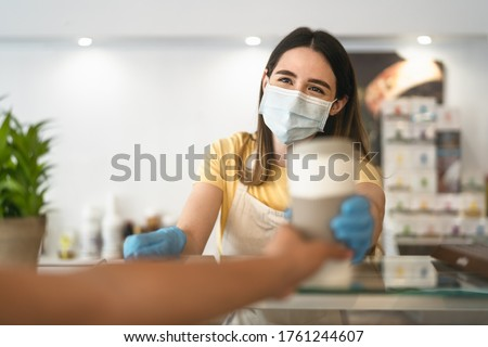 Bar owner working only with take away orders during corona virus outbreak - Young woman worker wearing face surgical mask giving coffee to customer - Healthcare and drinks concept