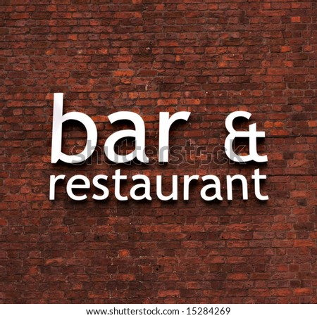 Bar & restaurant sign set on a very old red brick wall