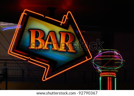 Bar sign arrow showing the way in a nightclub area.