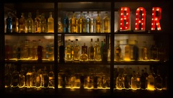 BAR sign with lights in the dark with bottles of alcohol.
