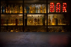 BAR sign with lights in the dark with bottles of alcohol and empty tabletop.