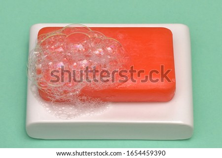 Bar soap with bubbles and soap dish