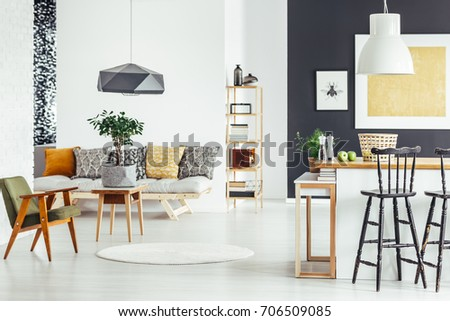 Bar stool at kitchen countertop in multifunctional interior with green chair and sofa #706509085