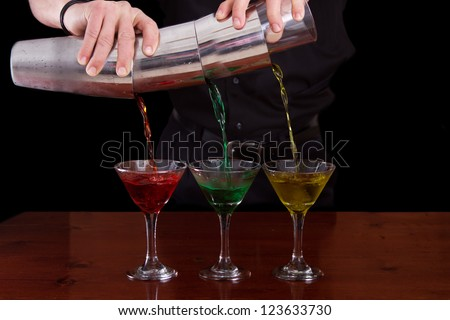 bar tender pouring three different color martinis in one fluid motion