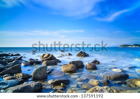 Baratti bay, rocks in a blue ocean under a clear sky on sunset. Tuscany, Italy.