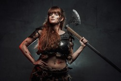 Barbaric and brown haired woman viking wielding two handed axe and dressed in dark armour poses in dark smokey background.