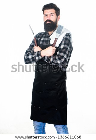 Barbecue accessories. Bearded man holding grill gripper tools. Hipster in apron with metal utensils for barbecue grill. Grill cook. Cooking barbecue. Preparing food on grill using a barbecue set.
