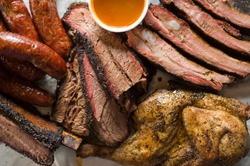 Barbecue catering platter with variety of meats. Traditional Texas BBQ: Beef brisket, beef ribs, pork ribs, sausage links, black pepper roasted chicken, and turkey served with homemade sauce.
