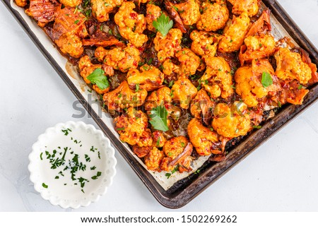 Barbecue Cauliflower Wings on a Baking Sheet with Sauce.  Healthy Baked Cauliflower Appetizer Photo. Foto stock ©