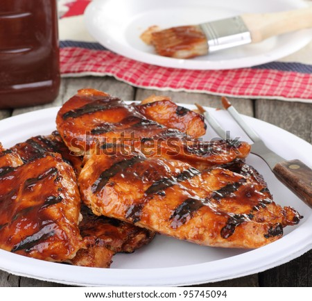 Barbecue chicken breast on a paper plate