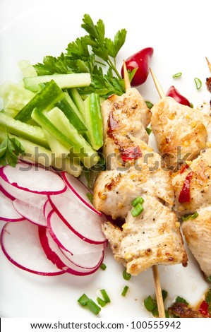 barbecue chicken on a white plate with vegetables