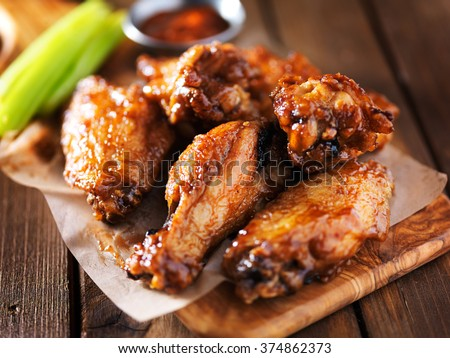 Photo of  barbecue chicken wings close up on wooden tray shot with selective focus