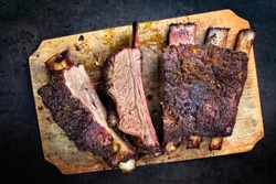 Barbecue chuck beef ribs with hot rub as top view sliced on a wooden cutting board