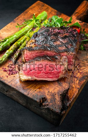 Barbecue dry aged wagyu entrecote beef steak with lettuce and green asparagus as closeup on an old rustic wooden cutting board