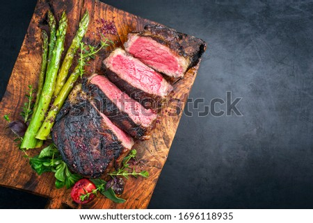 Barbecue dry aged wagyu entrecote beef steak with lettuce and green asparagus as top view on an old rustic wooden cutting board with copy space right