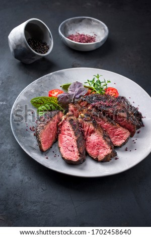 Barbecue dry aged wagyu entrecote beef steak with lettuce and tomatoes as closeup on a modern design plate