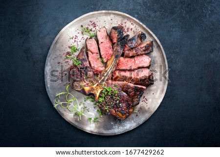 Barbecue dry aged wagyu porterhouse beef steak sliced with large fillet piece with herbs and red salt as top view on a modern design rustic plate with copy space