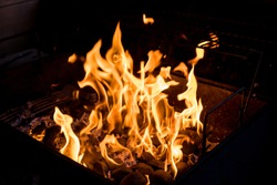 Barbecue Fire Grill on Black Background.burning charcoal. Focus is on Hot coals in the fire.burning charcoal background with fire and sparks.The coals smolder outdoor