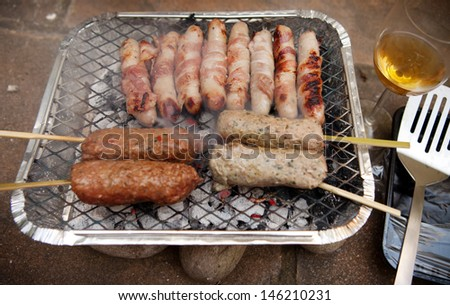 barbecue frying sausages and shish kebab. disposable bbq with meat skewer cooking on hot coals