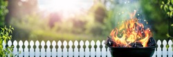 Barbecue Grill With Wood Fire In Backyard With Picket fence And Sunset Background