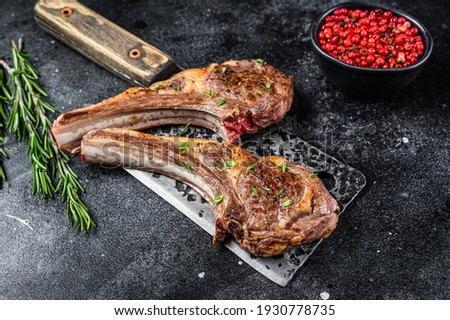 Barbecue grilled lamb chops on a butcher meat cleaver. Black background. Top view. Photo stock ©