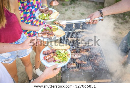 Barbecue in home garden, Host serving his guests - Group of friends making barbecue and having fun at private party