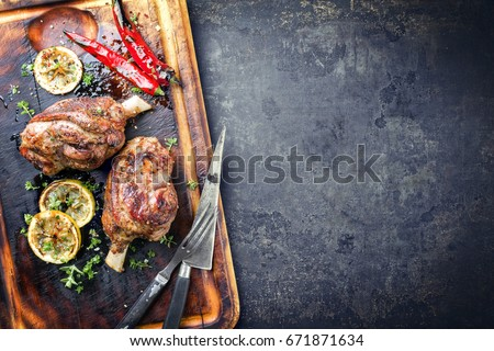 Barbecue Leg of Lamb with Tomato Chili Relish as top view on burnt cutting board  #671871634