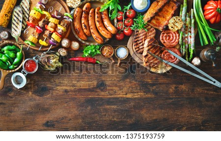 Barbecue menu. Grilled meat and vegetables on rustic wooden table with copy space for text #1375193759