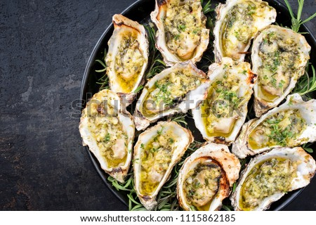 Barbecue overbaked fresh opened oyster with garlic and herbs offered as top view on a tray with copy space left #1115862185
