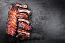 Barbecue pork spare ribs St Louis cut sliced with hot honey chili marinade as top view on an old rustic metal board with copy space right