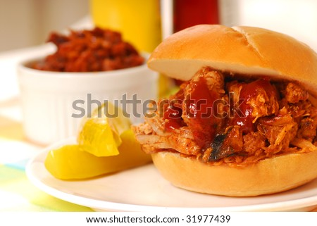 Barbecue pulled pork sandwich with baked beans and pickles
