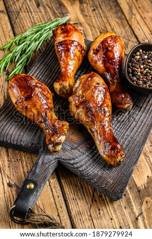Barbecue roasted chicken drumsticks on a wooden cutting board. wooden background. top view Stok fotoğraf ©
