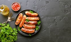 Barbecue sausage with fresh parsley on plate on a over black stone background with copy space. Top view, flat lay