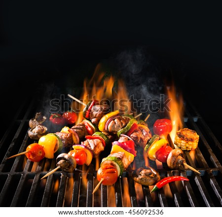 Barbecue skewers meat kebabs with vegetables on flaming grill #456092536