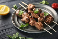 Barbecue skewers with juicy meat on metal plate